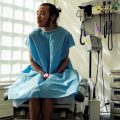 LGBTQ health; a genderqueer person sitting in a hospital gown sitting in an exam room