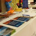 Table of colorful printed materials at the Fort Morgan International Music Festival
