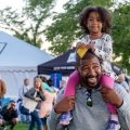 Smiling black daughter sits on smiling black dad's shoulders at a community festival