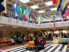 A variety of world flags hang in an atrium where community members mingle and sit at tables