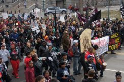 Large crowd marches down Colfax near the state Capitol building carrying signs and flags