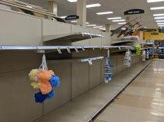Empty grocery store shelves with loofahs hanging in front