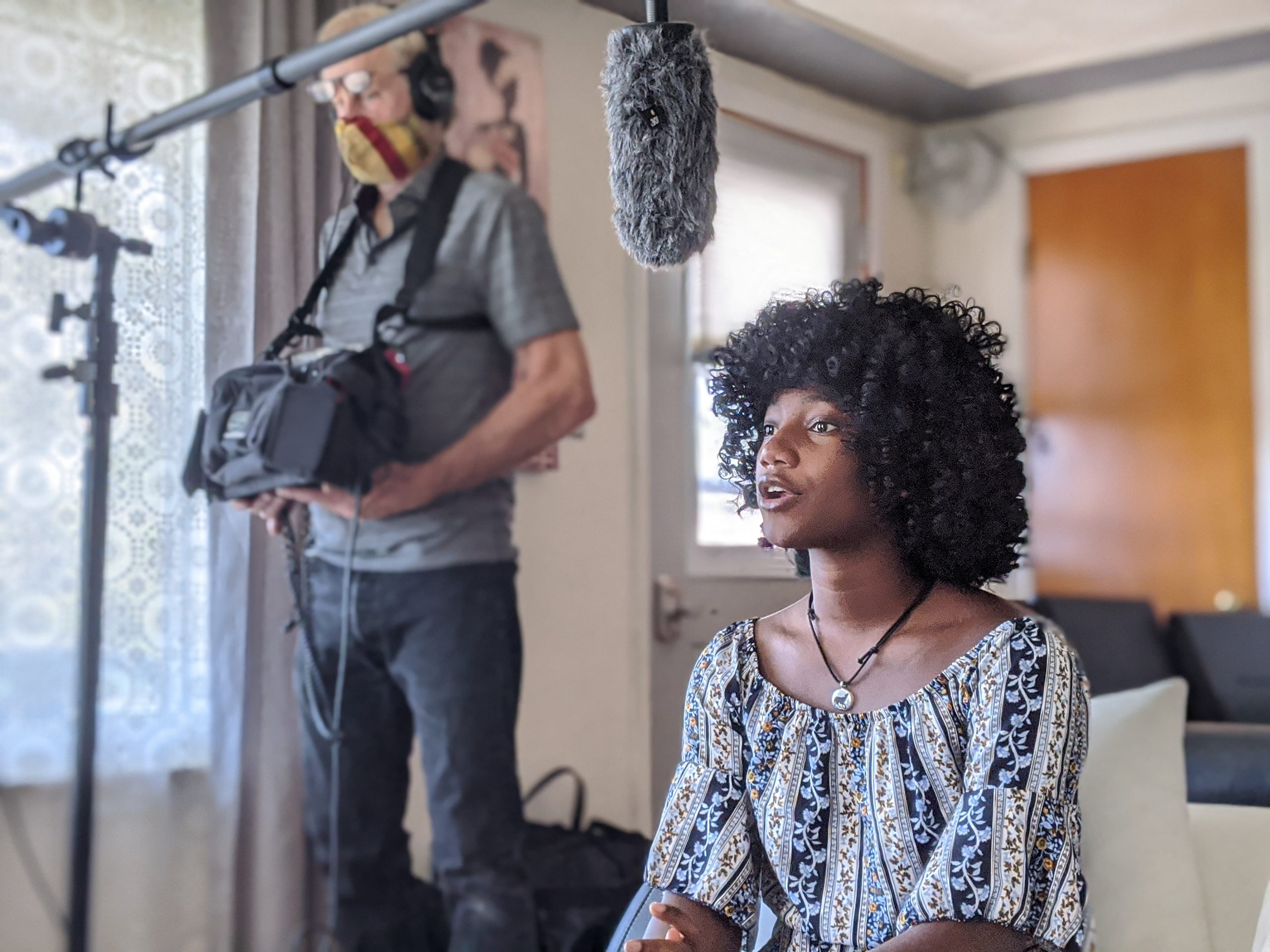 Young black woman speaks and genstures to a film crew