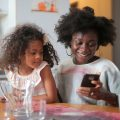 Black woman with a small girl in her lap holds a cellphone and smiles as she looks down at it