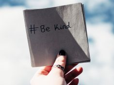 Hand holding a square piece of paper with the words written, #BeKind