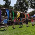 At Pueblo Pride, a line of people hold hands walking in a large circle with colorful flags behind them
