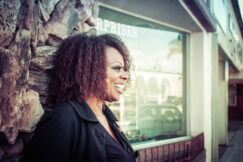 Black woman looks to the right and smiles standing in front of a building with a large window and stone siding